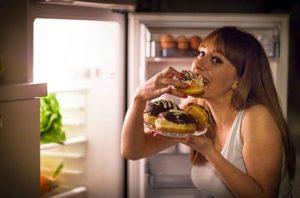 nő eszik a hűtőszekrény előtt
